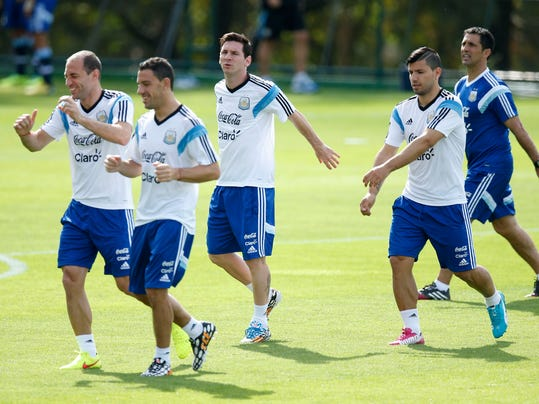 Argentina's Lionel Messi, center, warms up next to teammates Maxi Rodriguez, second left, Pablo Zabaleta, left, and Sergio Aguero, second right, during a training session in Vespasiano, near Belo Horizonte, Brazil, Wednesday, June 18, 2014.  Argentina plays in group F of the 2014 soccer World Cup. (AP Photo/Victor R. Caivano)