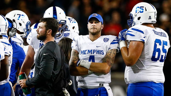 University of Memphis starting quarterback Riley Ferguson (right) walks outside an offensive huddle after leaving the game against University of Cincinnati with an injury in Cincinnati, Ohio.