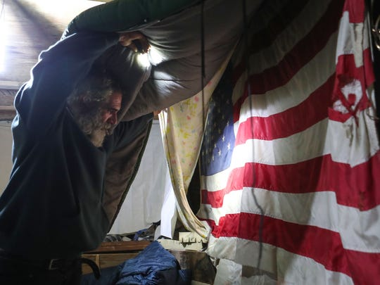 Inside of his home made from scrap wood and found items, Chris Hanning shows a prized possession, an American flag that he recycled after someone had thrown it away.