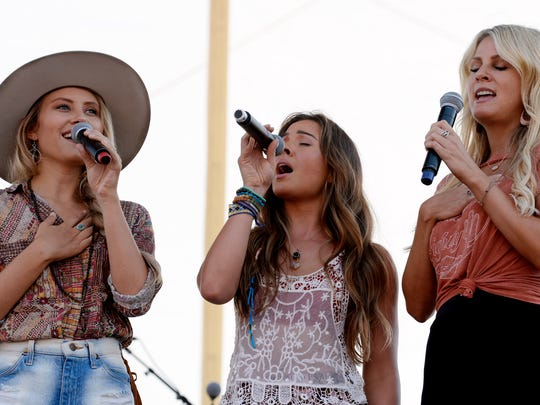 Hannah Mulholland, left, Naomi Cooke and Jennifer Wayne of Runaway June sing the national anthem at the Riverfront stage during the CMA Music Festival in 2018.