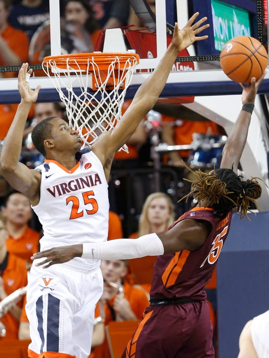 Virginia forward Mamadi Diakite (25) defends as Virginia Tech forward Chris Clarke (15) takes a shot during the second half of an NCAA college basketball game in Charlottesville, Va., Saturday, Feb. 10, 2018. Virginia Tech won the game 61-60 in overtime. (AP Photo/Steve Helber)