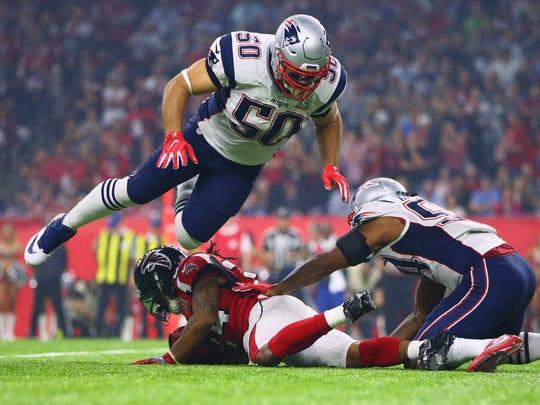New England Patriots linebacker Rob Ninkovich (50) leaps over Atlanta Falcons running back Devonta Freeman during Super Bowl LI at NRG Stadium.