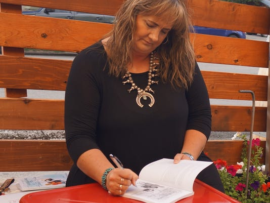 "Dana Williams signing her book, ""Conversations in the Beauty Shop"" at her book signing party at The Hidden Tap Tuesday, Oct. 3."