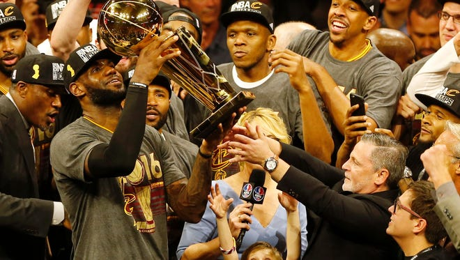 Cavaliers forward LeBron James, left, hoists the Larry O'Brien trophy with owner Dan Gilbert, right, after defeating the Golden State Warriors to win the NBA title in Oakland, California.