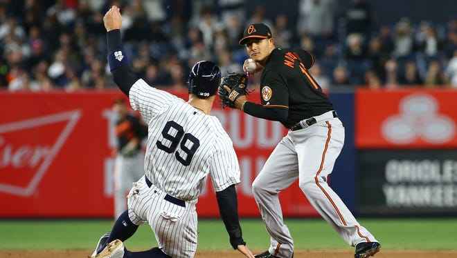 New York Yankees right fielder Aaron Judge (99) is forced out at second base by Baltimore Orioles shortstop Manny Machado (13) who throws to first base on a double play during the third inning at Yankee Stadium.