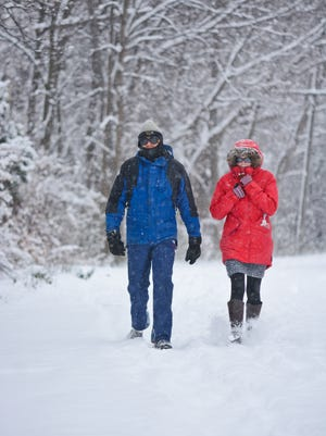 Scott Roberts and Alison Erskine walk down a snow-covered Fox River Trail on Sunday.