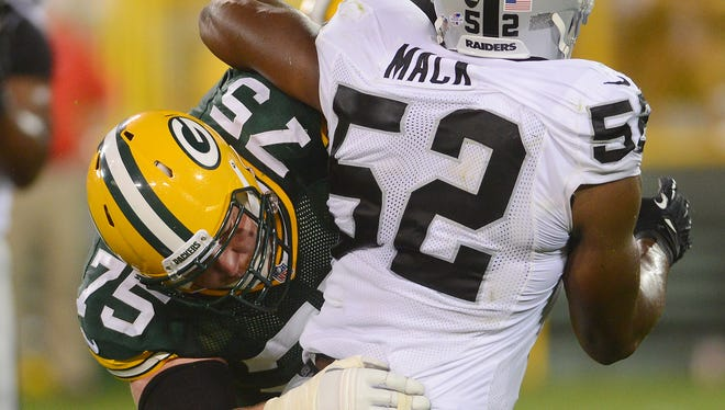Green Bay Packers lineman Bryan Bulaga (75) blocks on Khalil Mack (52) against the Oakland Raiders at Lambeau Field August 22, 2014.  Jim Matthews/Press-Gazette Media