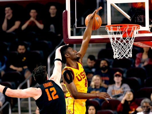 Southern California forward Chimezie Metu,right, reaches for a rebound next to Oregon State forward Drew Eubanks during the first half of an NCAA college basketball game Saturday, Feb. 17, 2018, in Los Angeles. (AP Photo/Ringo H.W. Chiu)