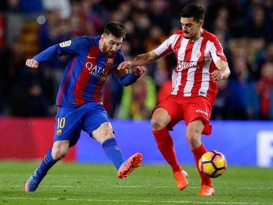 FC Barcelona's Lionel Messi, left, duels for the ball against Sporting Gijon's Sergio Alvarez during the Spanish La Liga soccer match between FC Barcelona and Sporting Gijon at the Camp Nou stadium in Barcelona, Spain, Wednesday, March 1, 2017. (AP Photo/Manu Fernandez)
