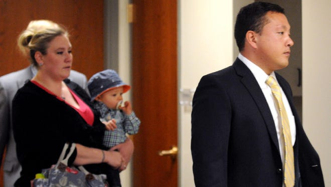 In this May 21, 2014 file photo, Marcus Kaarma, right, is followed into Missoula District Court by his wife Janelle with their child in Missoula, Mont.