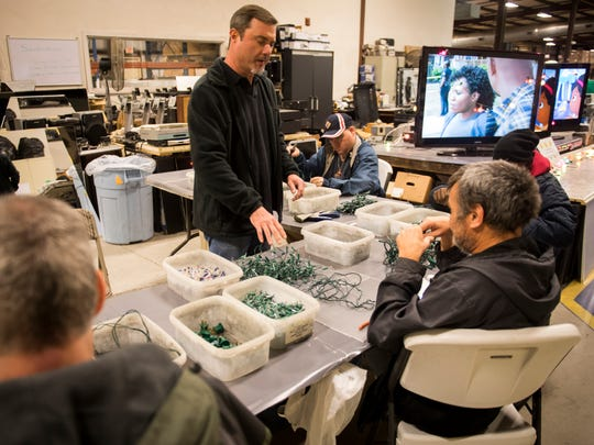 E-cycle manager Alan Champlin, center, works with Sunshine Industries employees as they disassemble donated Christmas lights on Thursday, Dec. 14, 2017.