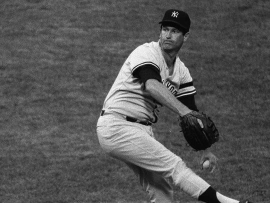 Tommy John of the New York Yankees prepares to fire