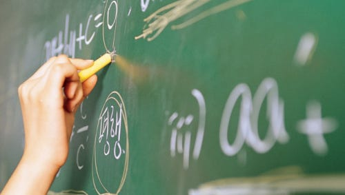 A stock image of a person writing on a chalkboard.