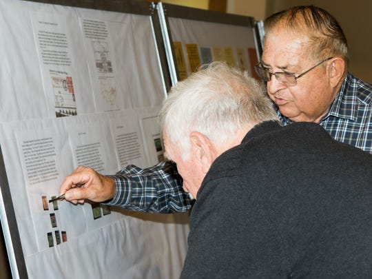 Mesilla Valley Stamp Club President Armando Angel explains the fine details of stamps to Ted Derruyter during the 26th Annual Mesilla Valley Stamp Show.