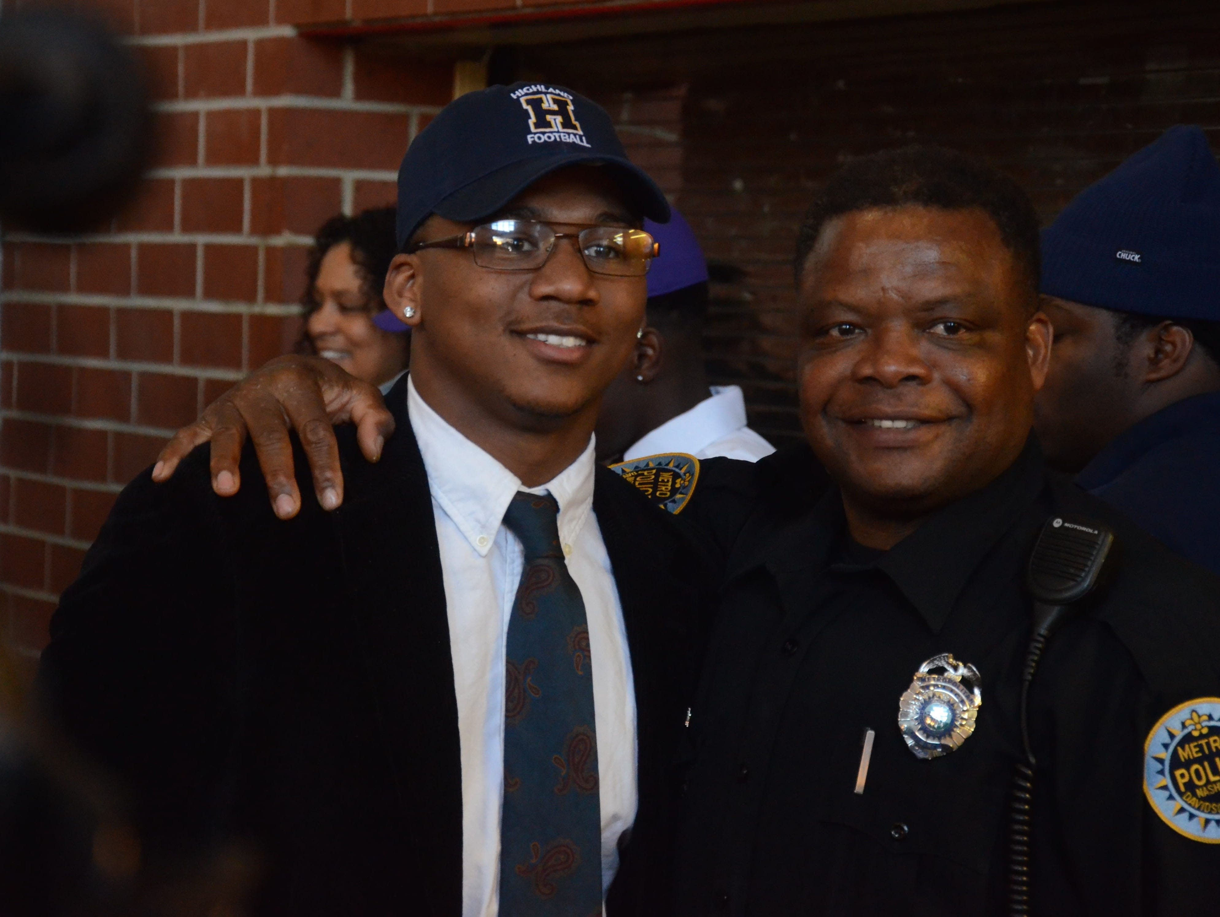 Pearl-Cohn senior A.J. Morris (left) poses for a photograph with one of his mentors, officer Paul Flournoy, after signing a letter of intent to play football at Highland Community College.