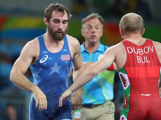 Vladimir Vladimirov Dubov faces Daniel Dennis, left, during men's freestyle wrestling competition in the Rio 2016 Summer Olympic Games at Carioca Arena 2.