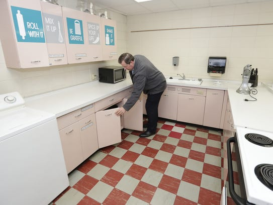 Superintendent Glenn Schlender looks through the 1960s era metal cupboards in the family and consumer science lab Wednesday at Luxemburg-Casco High School in Luxemburg. The area would roughly triple in size and be modernized if a proposed referendum passes.