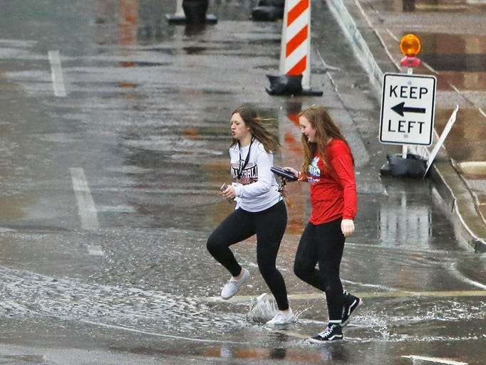 Pedestrians in the rain navigate through puddles along