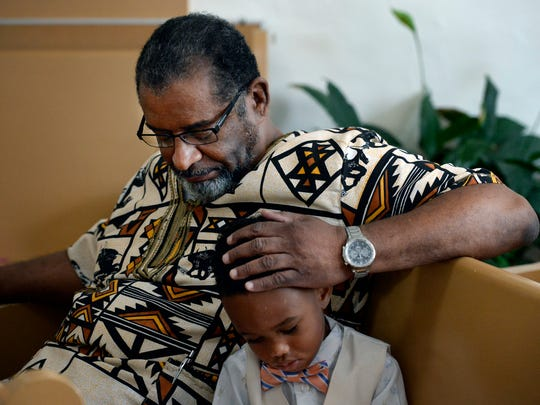 Dr. Lester Lewis Jr. prays with his grandson, Malcolm