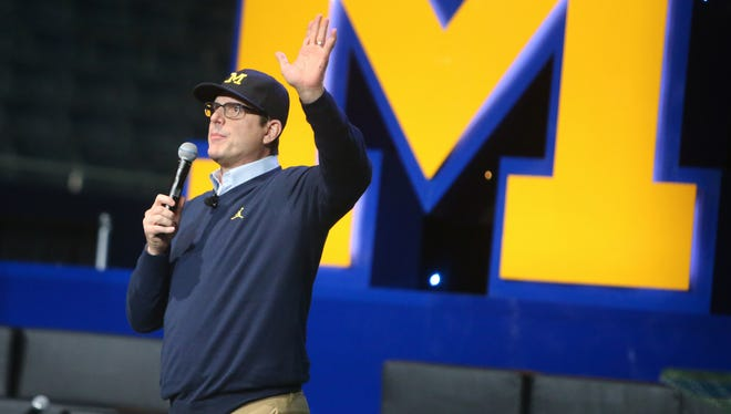 Michigan head coach Jim Harbaugh talks with fans during the Signing of the Stars event held at the Crisler Center in Ann Arbor on Wednesday, Feb. 1, 2017.