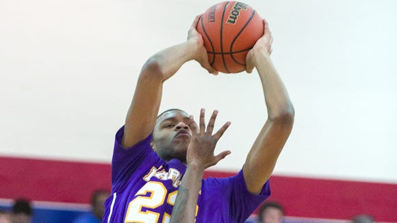Marion High School sophomore Reggie Jones (23) puts up a shot over the defense of Arsenal Tech High School senior Michael Jones (23) during the first half of varsity basketball action in a game of Indiana's Best Showcase at Marshall High School Dec. 23, 2013.