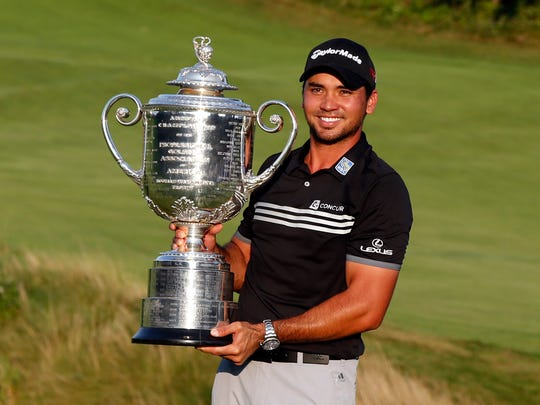 Jason Day poses with the Wanamaker Trophy after winning