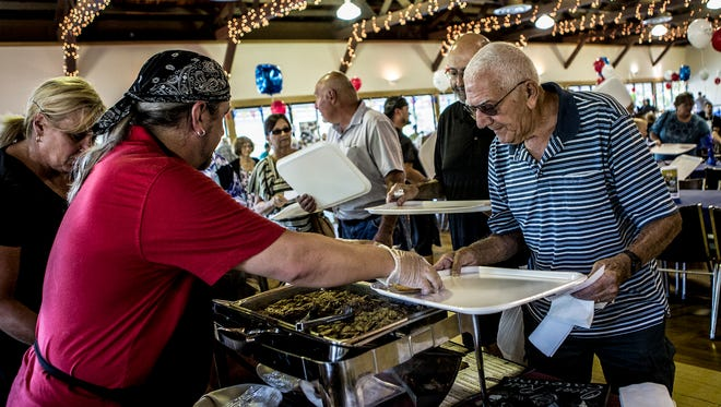 John Mathis holds out his tray waiting for a sandwich from Warehouse Steak and Stein at the 14th annual Taste of Coshocton. The event held at Coshocton Lake Park is a fundraiser for the United Way.