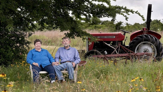 Anita and Jim McHaney sit underneath the tree on their property in Hearne, Texas, where they made the tough decision to stop farming.