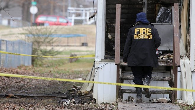 A fire investigator enters the house where a fire killed three in Bemis on Wednesday.