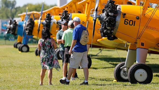 AirVenture visitors converse in front of a row of bi-wing planes during EAA AirVenture 2017 Saturday, July 29, 2017, at Wittman Regional Airport in Oshkosh, Wis.  July 29, 2017. Doug Raflik/USA TODAY NETWORK-Wisconsin