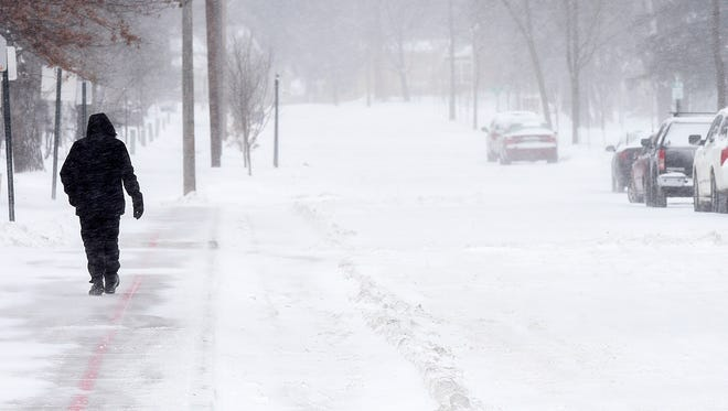 A pedestrian makes his way along Fifth Avenue SE through the blowing snow Tuesday, Jan.10, in St. Cloud.