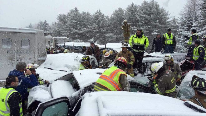 Rescue workers extract some collision victims from their car at the heart of a Feb. 25, 2015, pileup on Interstate 95 west of Bangor, Maine.
