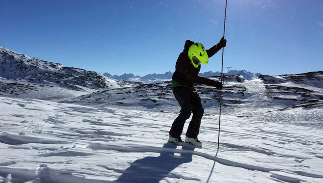 Geologist Katreen Wikstrom Jones using an avalanche probe to measure snow depth at Thompson Pass, Alaska.