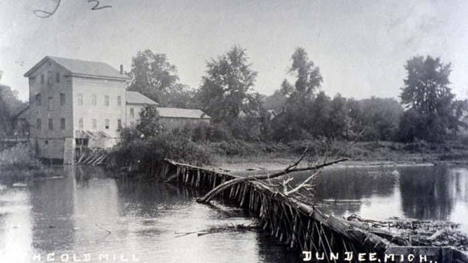 Photo shows the exterior of the Alfred Wilkerson Grist Mill in Dundee, circa early 1900s. The Alfred Wilkerson Grist Mill is a historic structure located along the River Raisin at 242 Toledo Street in Dundee. In 1935, Henry Ford worked to save and restore the mill, which was designated a museum in 1986 and placed on the National Register of Historic Places in 1990.