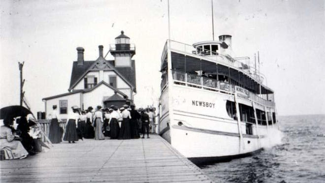 """This photo shows passengers boarding the Detroit-based tour boat, the """"Newsboy,"""" at the Monroe Piers (with the Hotel Lotus in the background), circa 1905."""