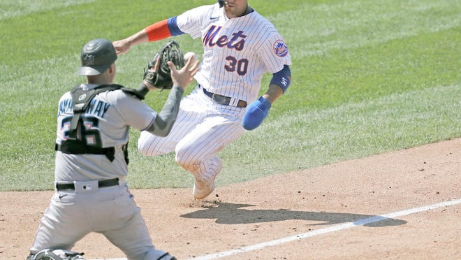 Miami Marlins catcher Ryan Lavarnway prepares to tag out New York Met Michael Conforto (30) at the plate during the fifth inning of Sunday's game at Citi Field in New York.