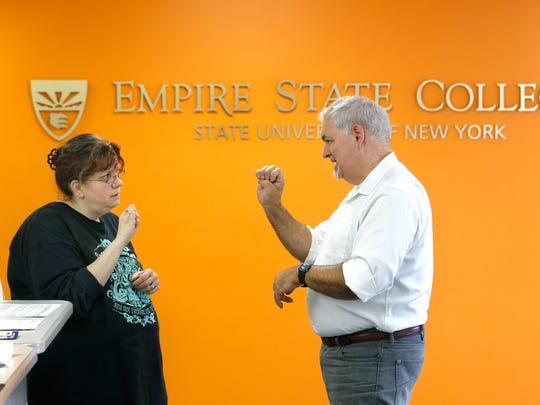 Catrina Osterman of Webster is taking an American Sign Language class at SUNY Empire State College. She engages in a conversation with her sign language instructor Thomas Coughlan of Pittsford at the college's local offices in Irondequoit earlier this month. Osterman was one of the students at the local Everest Institute when the college was suddenly closed a year ago.