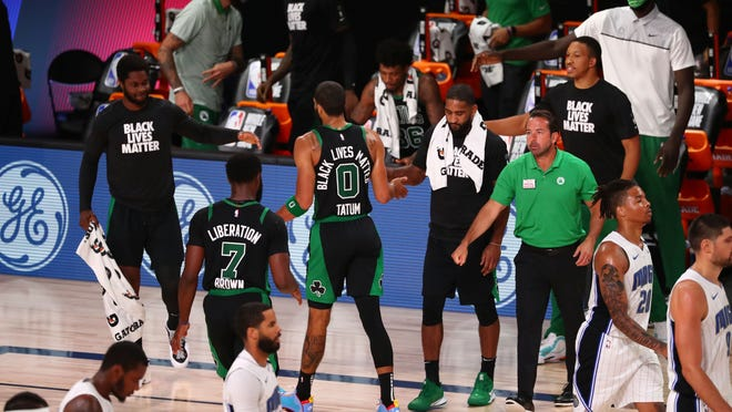 Boston's Jayson Tatum celebrates with teammates after making a basket to tie the game in the second half of Sunday's game.