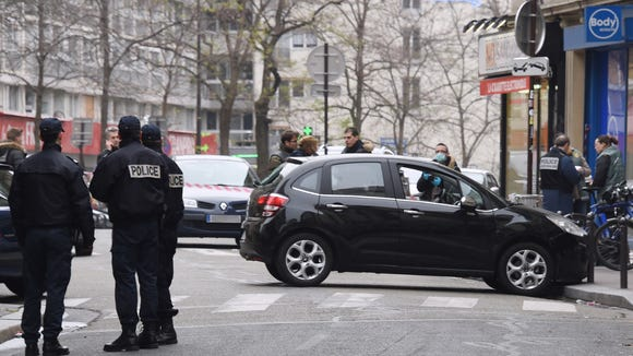 French police officers stand next to the car used by