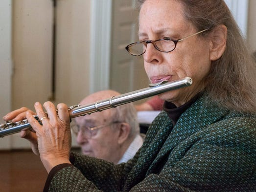 Retired attorney Cassandra Culin provides melody by means of flute.