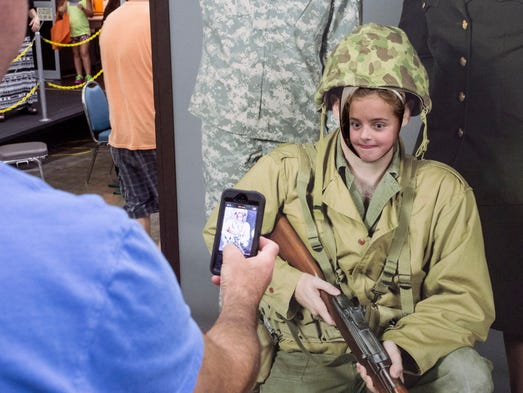 Barry Miller takes a cellphone shot of his daughter Roxie while she looks through a National Guard display in the South Wing during the last day of the State Fair.
