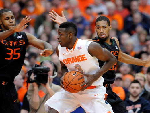 Syracuse Orange forward Jerami Grant (3) looks to take a shot over the defense of Miami Hurricanes forward James Kelly (35) and forward Donnavan Kirk (22).