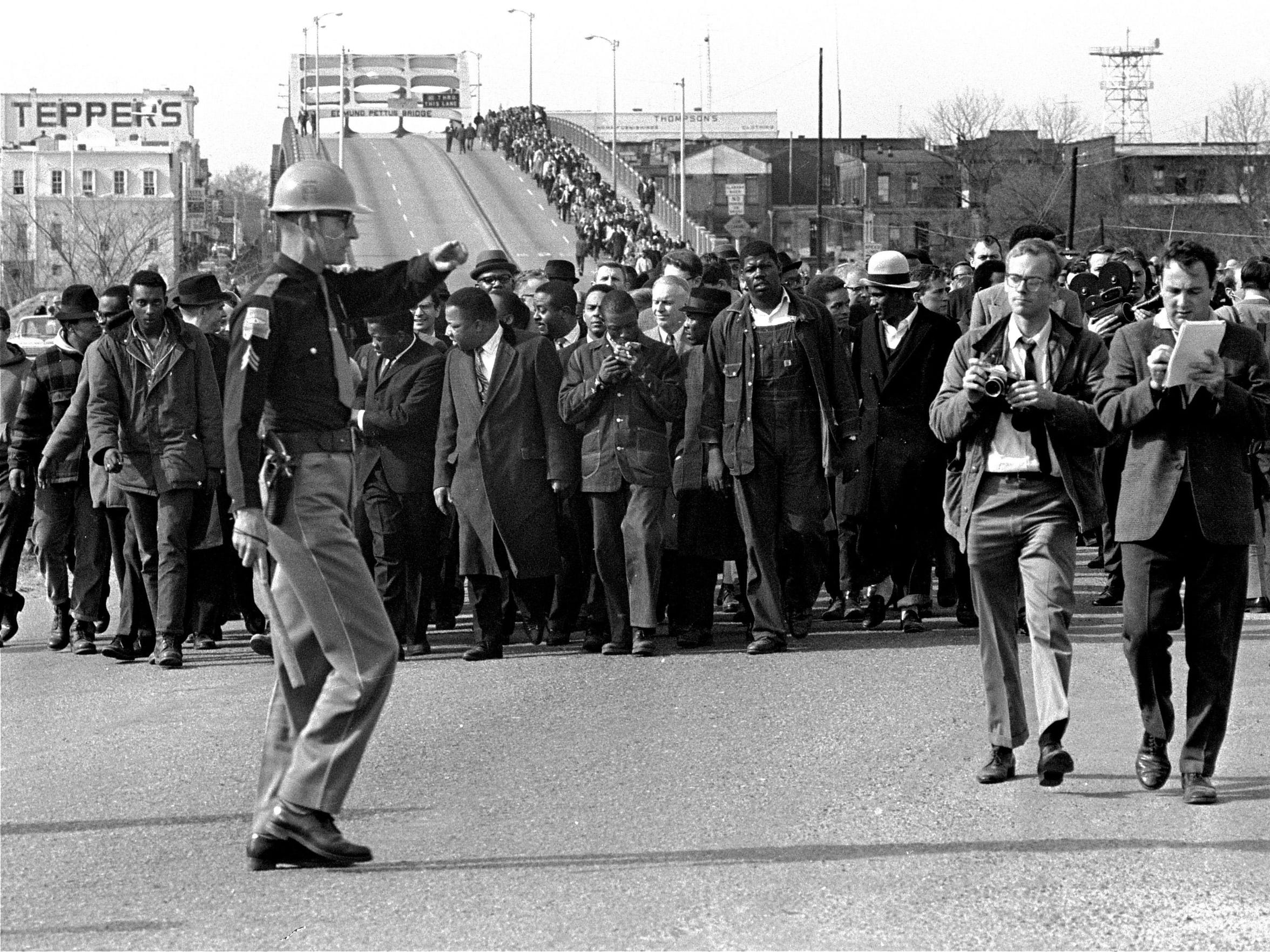 Demonstrators, including Dr. Martin Luther King Jr., stream over an Alabama River bridge at the city limits of Selma, Ala., on March 10, 1965.