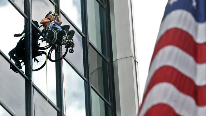 Molly Schneider of Cincinnati waves to friends and family below as she rappels down the Chase Bank building. Molly rappelled down the building in her wheelchair to raise money for Gracehaven the residential home and programming for minor victims of sex trafficking.The event was held August 8, 2020.