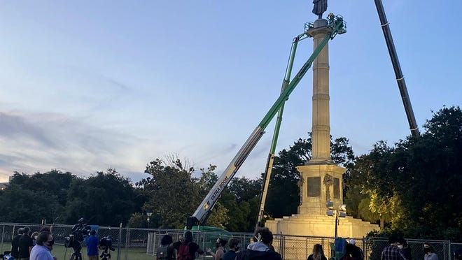 """People gather in Marion Square in the historic South Carolina city of Charleston, early Wednesday, June 24, 2020, to watch the removal of a statue of former vice president and slavery advocate John C. Calhoun. In the wake of protests and unrest, city council members voted Tuesday to remove the statue and place it permanently at """"an appropriate site where it will be protected and preserved.â€"""