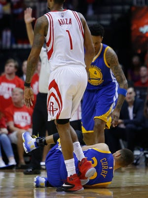 In this Sunday, April 24, 2016 photo, Golden State Warriors guard Stephen Curry (30) is injured on the final play during the first half of Game 4 in the first round of the NBA playoff series against the Houston Rockets, in Houston. Golden State's record-setting run toward a second consecutive NBA championship may come down to an MRI on the sprained right knee of Stephen Curry. The NBA's reigning MVP missed the second half of a win over the Houston Rockets in Game 4 on Sunday and was expected to have the medical test later Monday. (Karen Warren/Houston Chronicle via AP) MANDATORY CREDIT