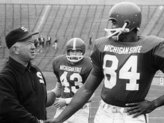 Michigan State coach Duffy Daugherty, left, shakes