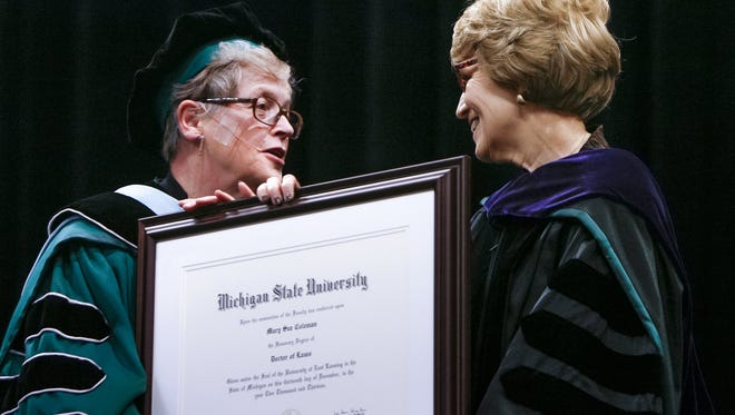MSU President Lou Anna Kimsey Simon, presents University of Michigan President Mary Sue Coleman with an Honorary Degree of Doctor of Laws during MSU's 2013 Fall Commencement, Friday, Dec. 13, 2013, at the Breslin Center in East Lansing.