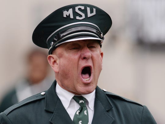 Glen Brough, visual and field coordinator, yells out to the band as they take the field and perform before the game against Michigan on Saturday, Oct. 29, 2016 at Spartan Stadium in East Lansing.