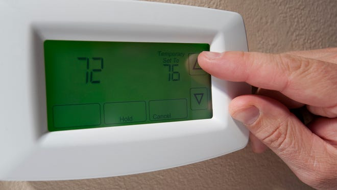 Changing the temperature on a digital thermostat.